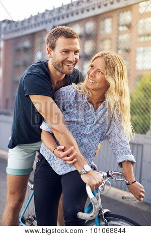 Happy Sweethearts Riding Bicycle At The Street