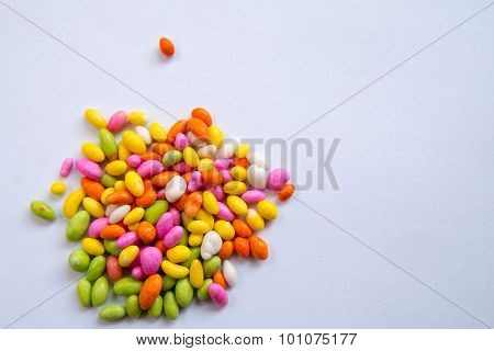 Small mixed high contrast color candies on a white background