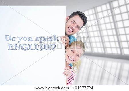 Smiling young couple hiding behind a blank sign against abstract room