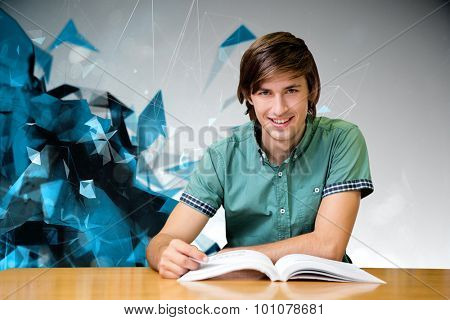 Student sitting in library reading against angular design