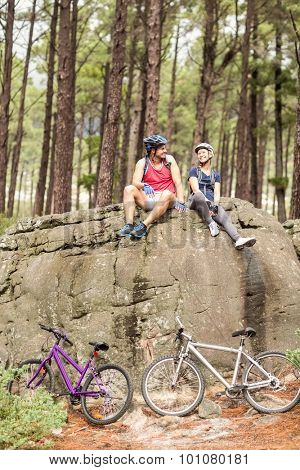 Young happy biker couple sitting on a rock in the nature