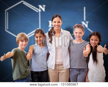 Cute pupils and teacher smiling at camera in computer class against blue chalkboard
