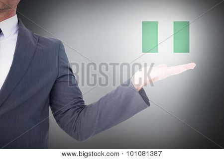 Businessman with his hand out against grey background
