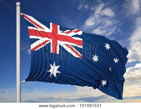 Waving flag of Australia on flagpole, on blue sky background.