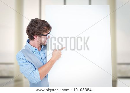 Smiling handsome man pointing at billboard against window overlooking city