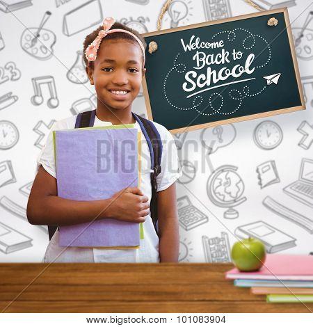 Little girl holding folders in school corridor against overhead of wooden planks