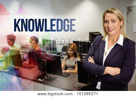 The word knowledge against computer teacher smiling at camera with arms crossed