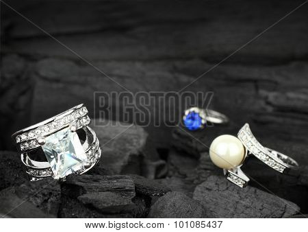 Few Jewelry Rings With Brilliants, Gems And Pearl On Dark Coal Background, Soft Focus