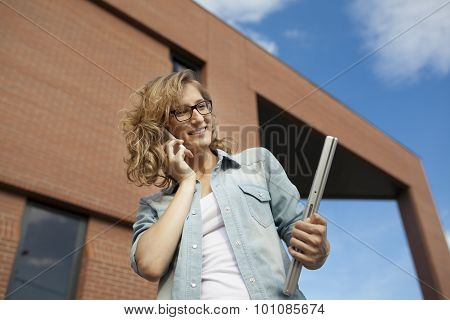 Young businesswoman smiling while calling on mobile phone holding laptoip in hand
