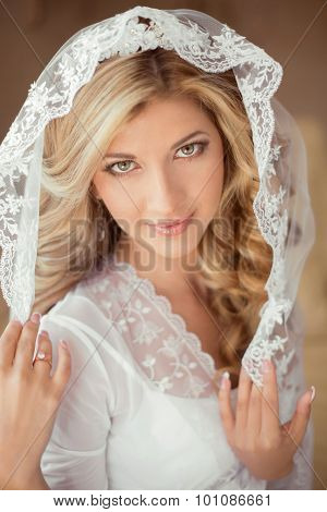 Portrait Of Beautiful Bride Wearing In Classic White Veil. Attractive Girl With Makeup And Long Curl