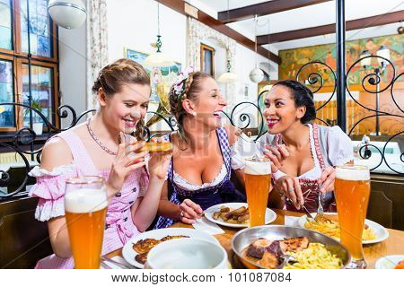 Women in Bavarian restaurant eating food, view over the table on the dishes