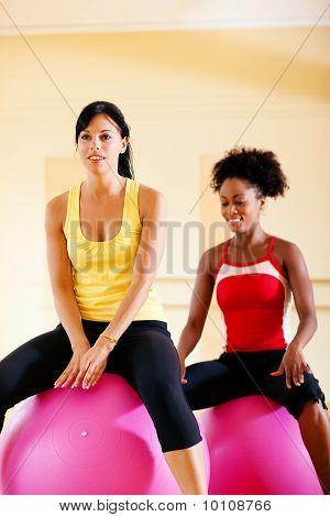 Dos mujeres con la bola de la aptitud en el gimnasio