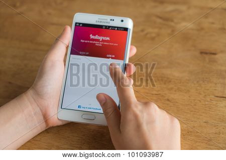 Loei, Thailand - August 7, 2015: Hand holding samsung galaxy note edge with mobile application for Instagram on the screen