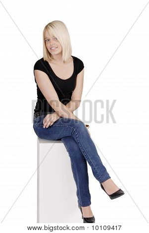 Young Blond Woman In Jeans Sitting On A Pilar