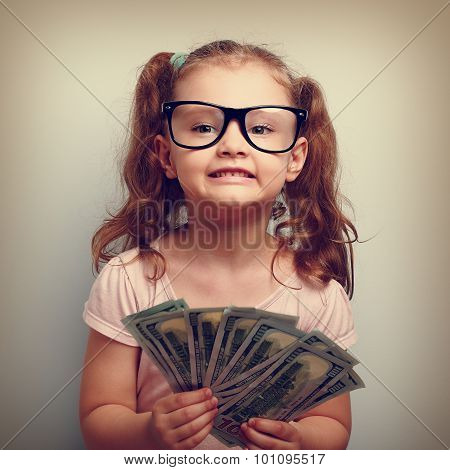 Fun Emotional Small Kid Girl In Glasses Holding And Showing Dollars. Happy Winner. Vintage Portrait