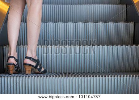 Business Woman In High Heels Standing On Escalators Stairway