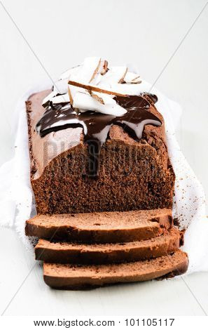 Loaf of chocolate cake with chocolate ganache frosting and coconut pieces