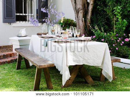 Table setting for an outdoor garden party with neutral nude color scheme