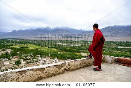 Young monk mn Thiksey Gompa roof in Ladakh, India