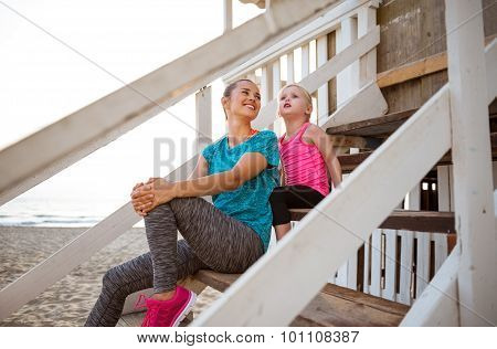 Mother And Daughter Sitting And Talking On Beach-house Steps