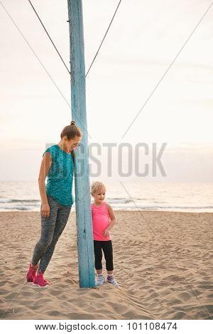Mother And Daughter In Fitness Gear Standing By Flagpole