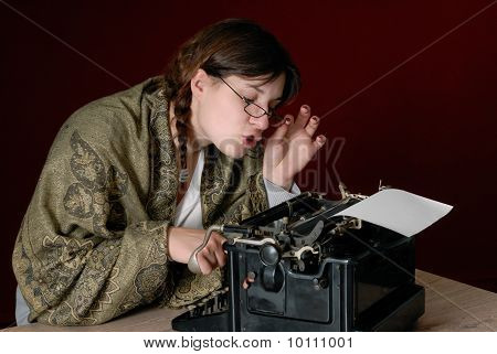 Female Author Typing On An Old Typewriter, Looking Trough Her Glasses