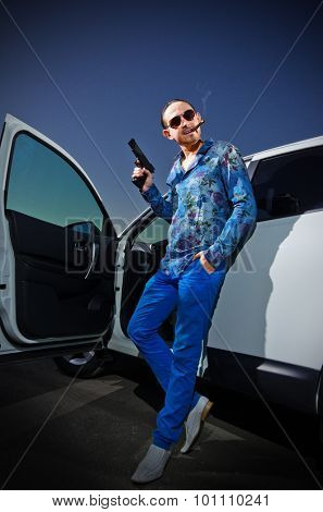 Gangster with cigar and gun near the car