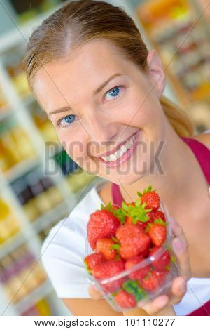 Shop assistant holding punnet of strawberries