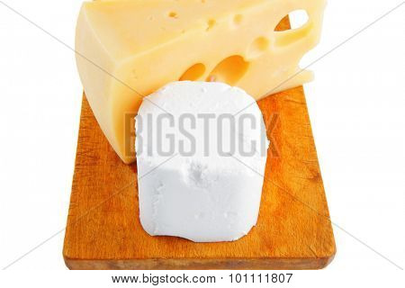 soft delicacy cheeses on small wood board