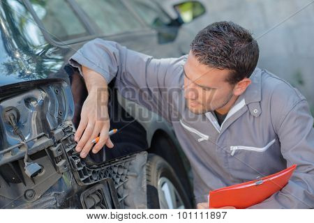 Mechanic taking notes of a car's faults