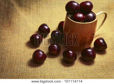 Wood Cup Full With Cherry On Sackcloth Background