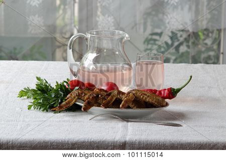 Chicken Wings Of A Barbecue And Compote In A Transparent Jug