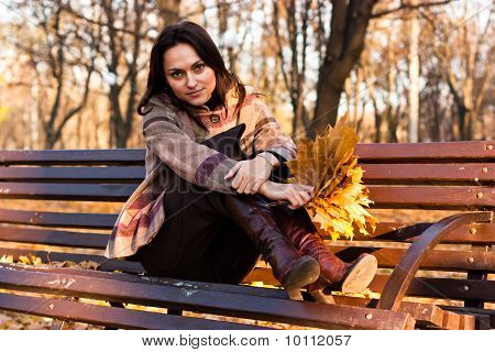 Beautiful Young Woman On A Bench In Autumn
