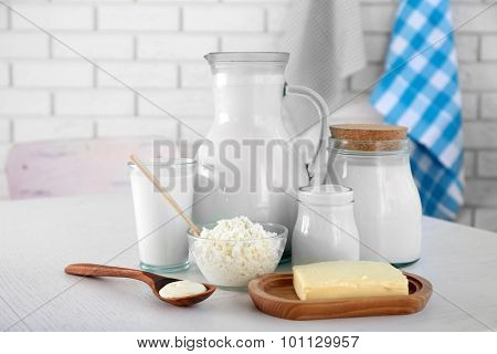 Dairy products on wooden table, on brick wall background