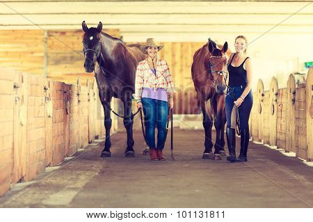 Cowgirl And Young Woman In Stable With Horses.