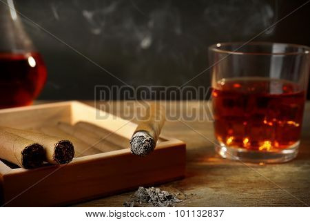 Cigars and burning one with cognac on wooden table on black background