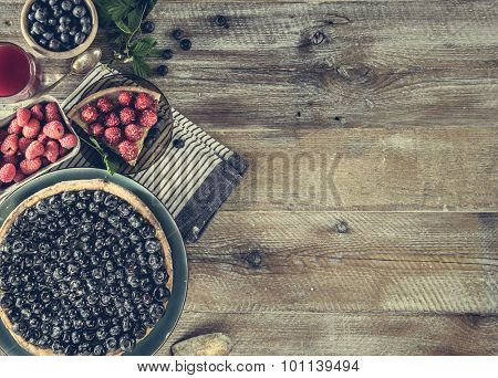Tart with blueberries and juice on a wooden background with space for text. top view