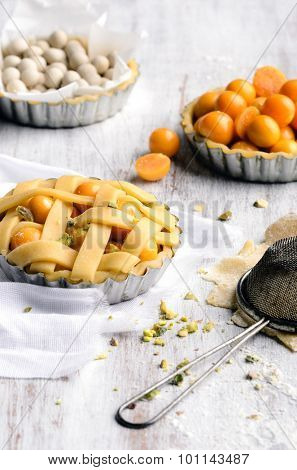 Fruit tart with lattice and raw baking ingredients in the background with vintage sieve