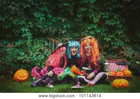 Group of cute girls in wigs and Halloween costumes sitting on green grass and looking at camera