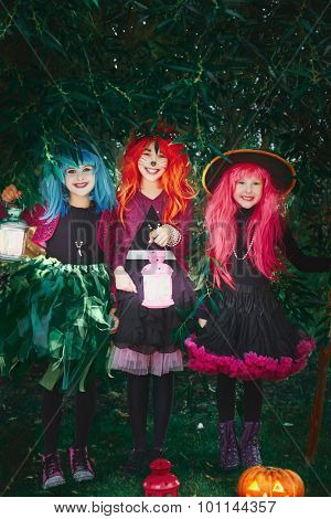 Cute girls in Halloween attire holding lanterns and looking at camera