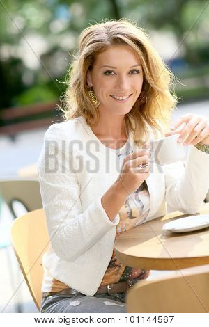 Active woman sitting at coffee place table and drinking tea