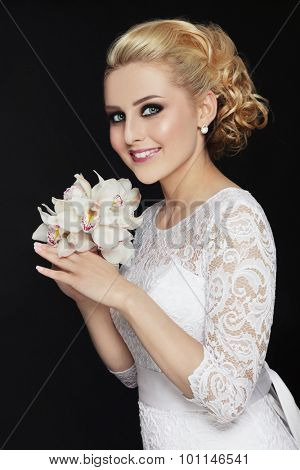 Young beautiful happy smiling slim blonde bride in lacy dress with stylish prom hairdo