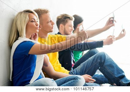 Group of happy students being on a break taking selfie. Focus on a grimacing girl. Background is blurry.