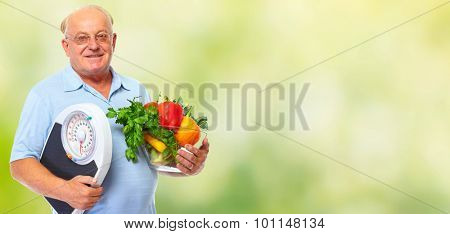 Elderly man with scales and vegetables over green background.