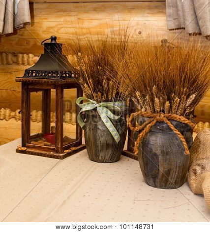 Wooden pots with a sheaf of wheat ears, interior of hunting lodge