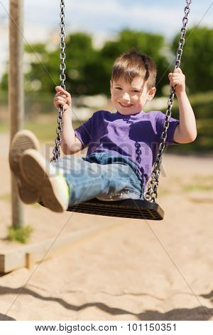 summer, childhood, leisure, friendship and people concept - happy little boy swinging on swing at children playground