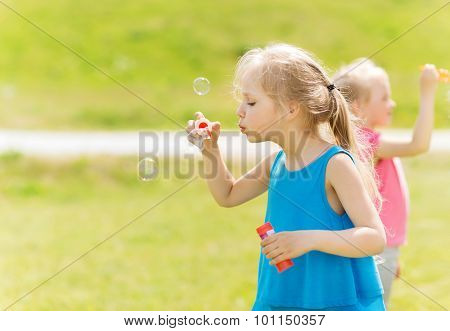 summer, childhood, leisure and people concept - group of little girls blowing soap bubbles outdoors