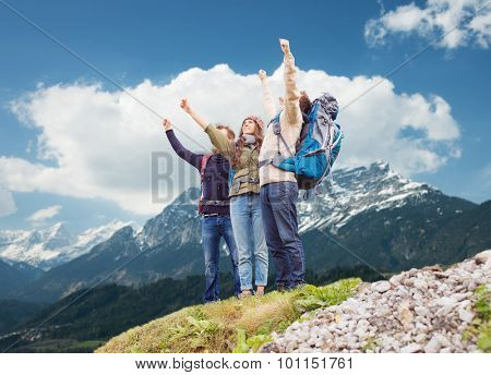 travel, tourism, hike, gesture and people concept - group of smiling friends with backpacks raising hands over mountains background