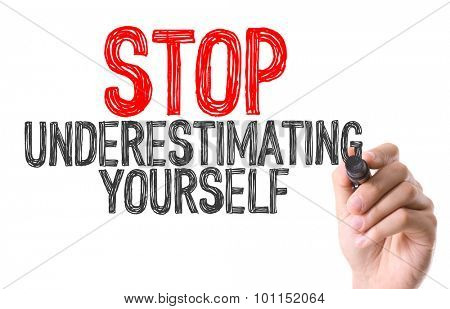 Hand with marker writing the word Stop Underestimating Yourself