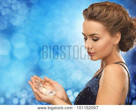 people, holidays and glamour concept - smiling woman in evening dress with diamond over blue lights background